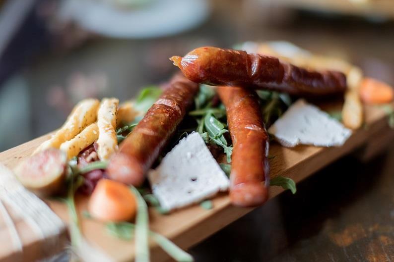 Korv serveras på bräda med pommes och örter