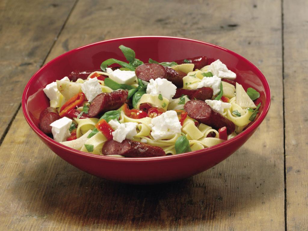 Tallrik med en pastasallad med korv, ost och grönsaker