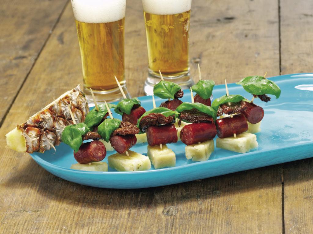 Bricka med spett med korv, tomat och ananas samt glas med öl